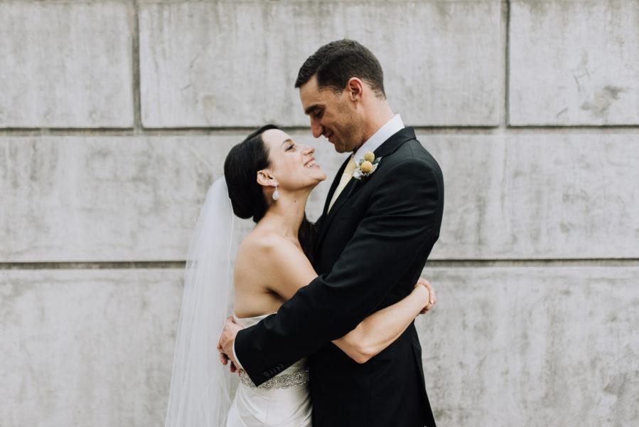 happy bride and groom cuddling outside Kehila Centre Toronto