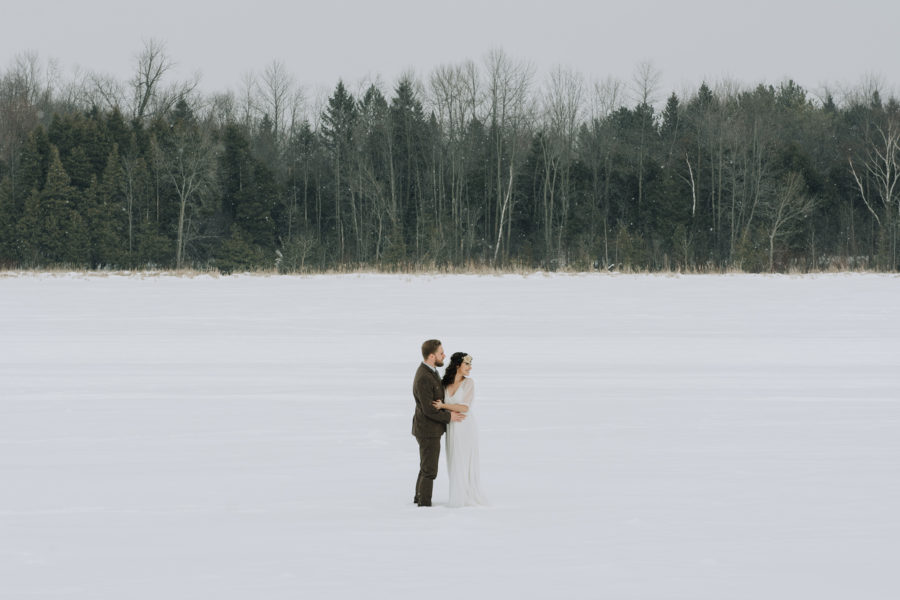 bride and groom cuddling on frozen lake in Peterborough