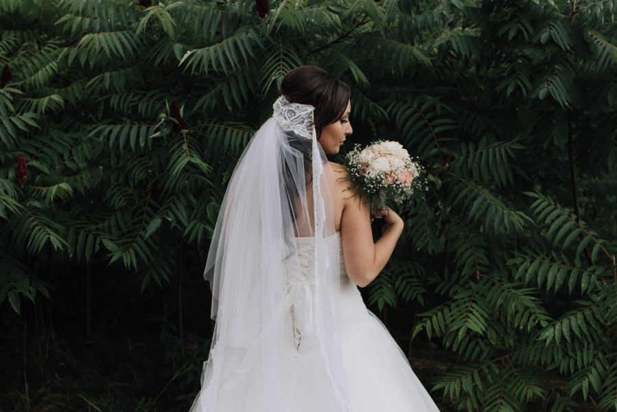 Bride holding bouquet in lush green foliage